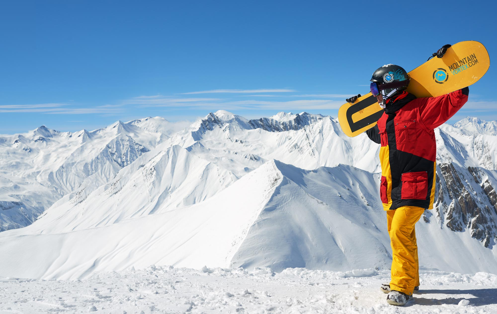 Mountain Vortex snowboarder holds snowboard over his shoulders